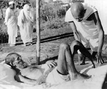 Gandhiji giving massage,to a leper patient, the Sanskrit scholar Parchure Shastri, at Sevagram Ashram in 1940. Source: Wikimedia Commons
