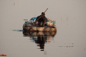एक अस्थायी बेड़े पर यमुना से प्लास्टिक के थैले इकठे करता यह आदमी एक महत्वपूर्ण काम कर रहा है । Source: Koshy Koshy/Flickr