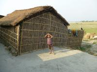 A boy stands outside his home on a spur