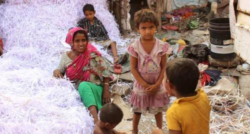 In aroadside ghetto, Akila Bibi and others after a day's hard work, separating white paper shreds from the colored ones for recycling. Earning Rs 3 a kg, they manage 30 kg to 50 kg a day. (Photo by Manipadma Jena)